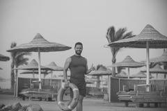 Человек с красным кольцом жизни на пляже Стоковые Фото