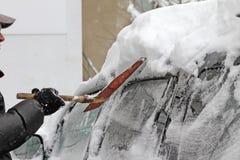 Человек с лопаткоулавливателем металла очищает автомобиль от снега на улице после большой пурги в городе, всех автомобилях под сн стоковое фото rf