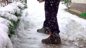 Человек с лопаткоулавливателем снега очищает тротуары в зиме