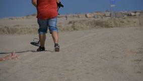 Человек с металлоискателем идет вдоль песчаного пляжа на Seashore движение медленное акции видеоматериалы