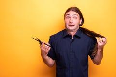 Человек с отчаянным взглядом думая волос вырезывания с ножницами стоковые фотографии rf