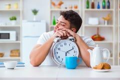 Человек с падать будильника уснувший на завтраке Стоковое Изображение RF