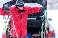 Человек с перчатками устанавливает цепи снега в покрышку автомобиля в зиме на снег стоковые изображения