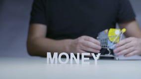 Человек с покупками вагонетки и карточка банка на деньгах слова предпосылки сток-видео