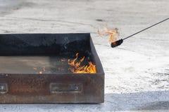 Человек с помощью факелу воспламеняет бензин в железной коробке стоковая фотография