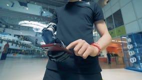 Человек с простетической рукой печатает на телефоне Человек с рукой робота