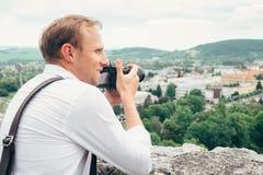 Человек с профессиональным изображением ландшафта взятия камеры фото стоковое фото