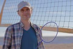 Человек с ракеткой бадминтона на пляже стоковые изображения rf