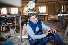 Человек с раненой рукой после аварии на работе в мастерской плотничества Стоковые Фотографии RF
