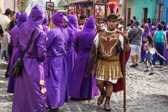 Человек с римским костюмом солдата идя вдоль фиолетовых облачённых людей на шествии Сан Bartolome de Becerra в 1a Стоковые Фото