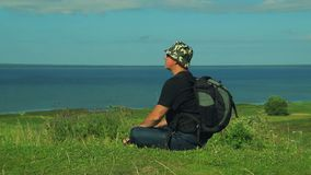 Человек с рюкзаком за его заднее сидит на краю горы и восхищает взгляд озера Съемка от акции видеоматериалы