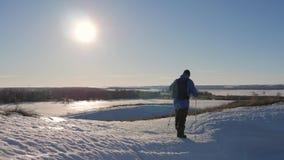Человек с рюкзаком и trekking ручками против фона гор зимы, красивого захода солнца, снега на холмах A сток-видео