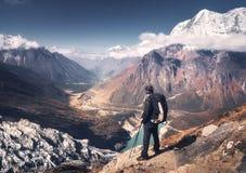 Человек с рюкзаком на горном пике на заходе солнца Стоковая Фотография RF