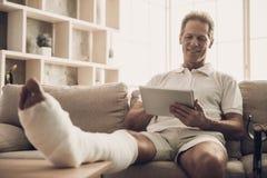 Человек с сломанной ногой сидит на софе и использует таблетку стоковые фото