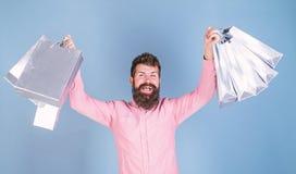 Человек с стильными хозяйственными сумками нося бороды и усика Победитель роскошного подарочного купона бутика на сини стоковое фото rf
