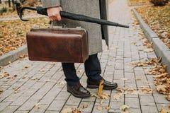Человек с сумкой и в пальто стоит на переулке осени стоковые фото
