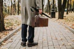 Человек с сумкой и в пальто стоит на переулке осени стоковые изображения rf