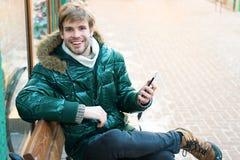 Человек с телефоном Холодное снаружи Пуща в снежке Свежий воздух Погода Snowy Ультрамодное пальто зимы зима способа предпосылки к стоковые изображения