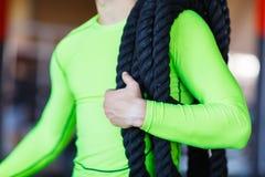 Человек с тяжелыми веревочками на его плечах стоковые фото