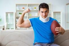 Человек с ушибом шеи наблюдая американский футбол дома Стоковые Изображения RF