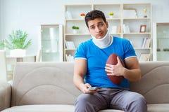 Человек с ушибом шеи наблюдая американский футбол дома Стоковое Изображение