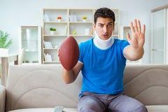 Человек с ушибом шеи наблюдая американский футбол дома Стоковое Фото