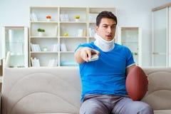 Человек с ушибом шеи наблюдая американский футбол дома Стоковые Фотографии RF
