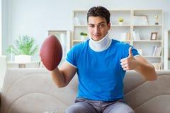 Человек с ушибом шеи наблюдая американский футбол дома Стоковые Изображения