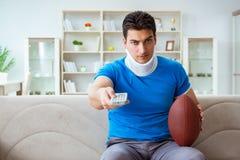 Человек с ушибом шеи наблюдая американский футбол дома Стоковое фото RF