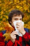 Человек с холодным ринитом на предпосылке осени Сезон гриппа падения Il стоковые изображения rf