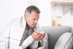 Человек с чашкой чаю для кашля на софе стоковое фото
