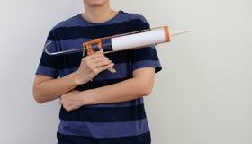 Человек с sealant силикона и оружием расчеканки в руках на белой предпосылке стоковые изображения