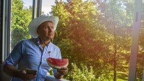 Человек с smarphone и ковбойской шляпой стоковое изображение rf