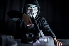 Человек тайны держа оружие над белой маской стоковая фотография