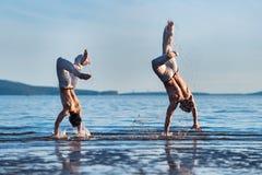Человек тренер capoeira и capoeira мальчика практикуя на пляже Человек и молодой бой парня поставленный игрой Стоковая Фотография