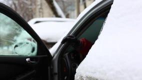 Человек трясет снег от снежных ног раньше сидит в автомобиле и приводе прочь видеоматериал