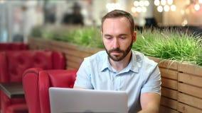 Человек уверенной кавказской этничности молодой используя ПК ноутбука на уютных кофейне или кафе сток-видео