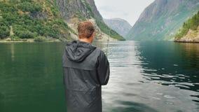 Человек удит на предпосылке гор в живописном фьорде Норвегии Удить в концепции Норвегии стоковые фотографии rf