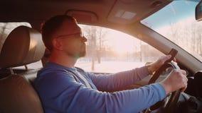 Человек управляет автомобилем автомобиля с телефоном кнопки в руке Лучи захода солнца и солнца через деревья на предпосылке сток-видео
