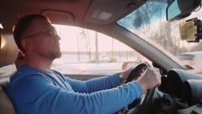 Человек управляет автомобилем и поет Лучи захода солнца и солнца через деревья на предпосылке акции видеоматериалы
