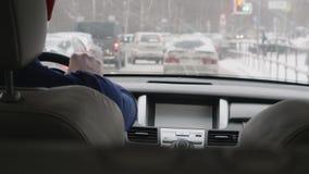 Человек управляет автомобилем на дороге вполне автомобилей и покрытой со снегом видеоматериал
