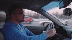 Человек управляет автомобилем поворачивая на перекрестную дорогу видеоматериал