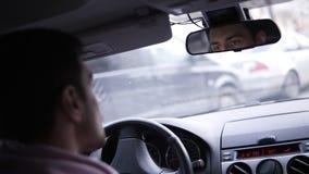 Человек управляет автомобилем Сторона отражения в зеркале заднего вида корабля Час пик в городе Отснятый видеоматериал от плеча акции видеоматериалы