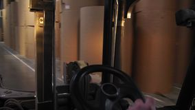 Человек управляет затяжелителем грузоподъемника вдоль storehouse с бумажными кренами сток-видео