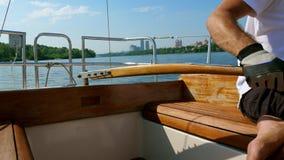 Человек управляет небольшой яхтой на реке около города сток-видео