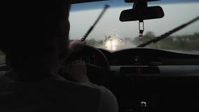 Человек управляя автомобилем в дожде в воде лобового стекла капая акции видеоматериалы
