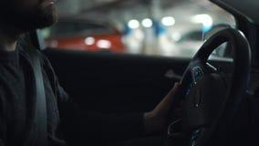 Человек управляя автомобилем через парковку и ищет место для того чтобы припарковать или управляет прочь сток-видео