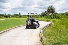 Человек управляя тележкой гольфа на пути Стоковые Фотографии RF