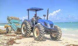 Человек управляя трактором и очищая пляж стоковая фотография rf
