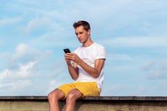 Человек усаженный на пристань в тропическом положении используя его смартфон Небо с облаками как предпосылка стоковое фото